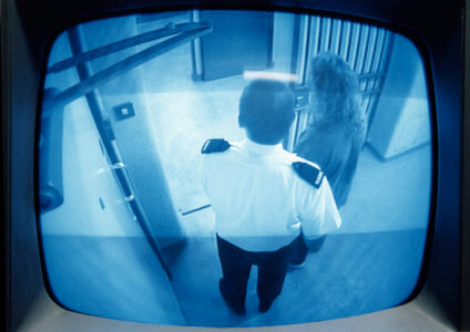 A TV monitor shows a police officer leading a detainee to a police cell.