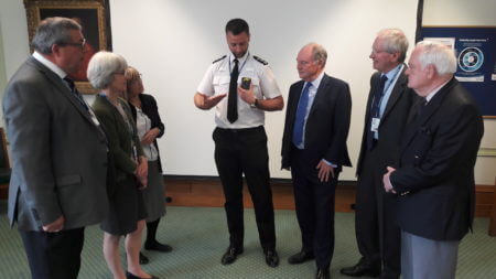 Chief Inspector Damian Pettit demonstrating the body worn video technology to members of the TIE Committee