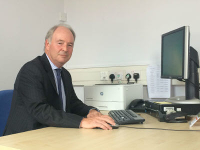 Warwickshire Police and Crime Commissioner Philip Seccombe sitting at a computer