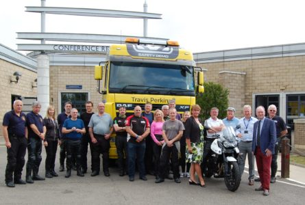 The class poses in front of a truck during the Rider Skills Day. Participants got the chance to climb into the cab to the limited visibility the driver would have of bikers.