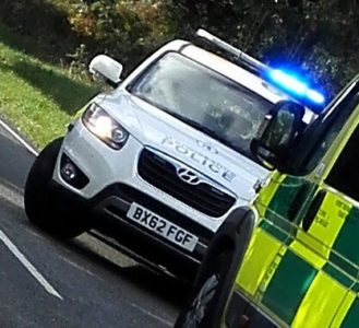 A police car pulls out from behind an ambulance