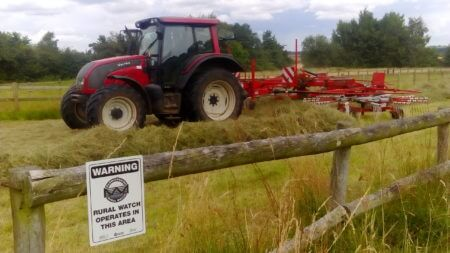 A tractor passes by a Warwickshire Rural Watch sign