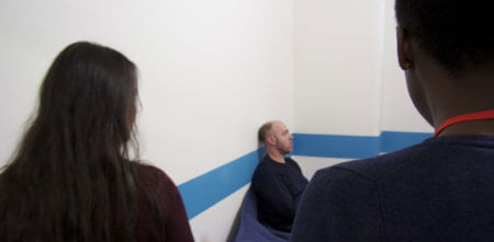 Two custody visitors in a cell with a detainee