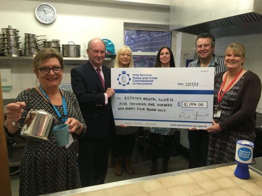 Warwickshire Police and Crime Commissioner Philip Seccombe presents a cheque for the funding to staff from Rethink Mental Illness during one of the drop-in coffee mornings at the centre in Warwick