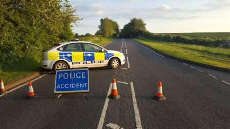 A police car sits across a closed road with 'Police accident' signs