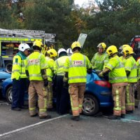Fire officers at a mock collision demonstrate how they extract casualties from a crashed vehicle.