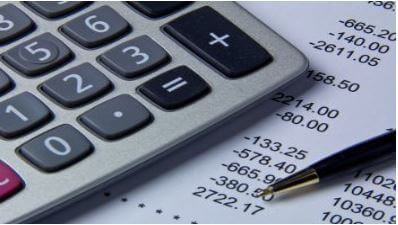An image of a calculator and some financial documents
