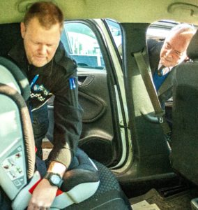 PC James Graham fits a child car safety seat watched by PCC Seccombe