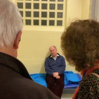 Independent Custody Visitors Justin Whitehorn and Janet Hodgson talk to Philip in the cell