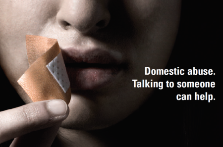 A woman peels a plaster from over her mouth. Caption reads 'Domestic abuse - Talking to someone can help'