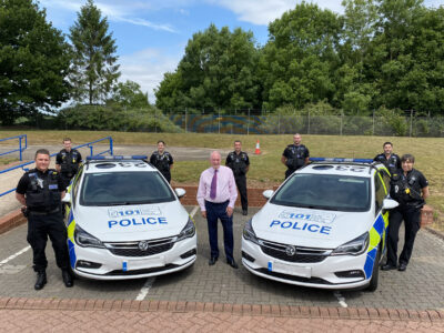 Warwickshire Police and Crime Commissioner Philip Seccombe stands between two police cars with members of the new Vehicle Crime Team at Greys Mallory.