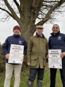 Rural Crime Advisors Bob Church (left) and Baz Bains (right) with Warwickshire Police and Crime Commissioner Philip Seccombe at Umberslade Road, near Earlswood, where one of the CCTV cameras is sited. A camera is fitted to the tree behind while the Rural Crime Advisors hold up signs warning of the CCTV coverage.