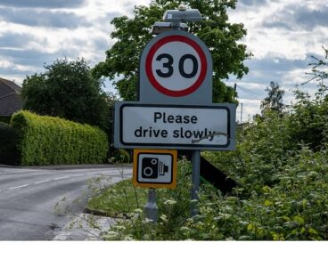 A road sign saying 'please drive slowly'