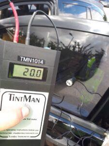 A handheld meter checks a car window's tint level