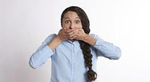 A young woman looks frightened and holds her hands over her mouth