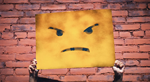 An angry face is held up on a banner