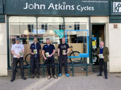 Philip Seccombe handing over copies of the Ultimate Guide to Cycling to staff at John Atkins Cycles in Leamington Spa