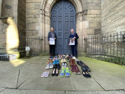 Philip Seccombe and Councillor Andy Crump stand behind 34 pairs of shoes.