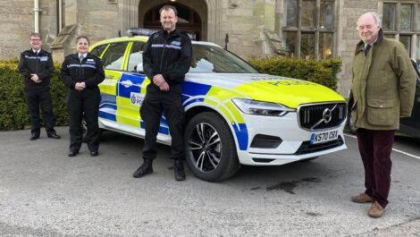 Officers and the PCC stand next to a police car