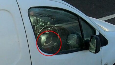 A van driver uses a phone while driving